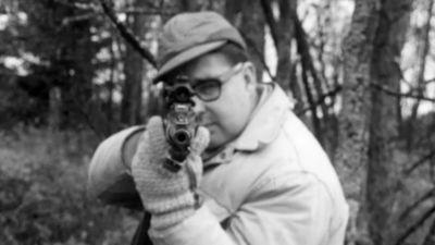 Man siktar mot tittaren på älgjakt, 1962