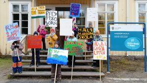 Flera barn står på trappan utanför Haddom skola. De håller i skyltar där det står att de vill rädda Haddom skola.