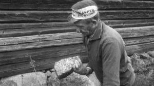 Man granskar sten, 1970