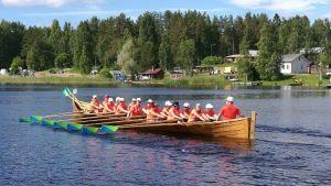 Kyrkbåt med roddare.