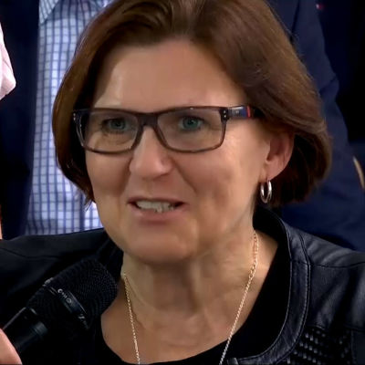 En kvinna med mikrofon framför sig.
