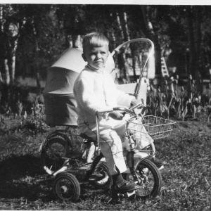 Poika istuu kolmipyöräisen päällä. Taustalla lastenrattaat.