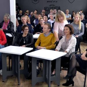 Flera människor sitter i publiken under en debatt.