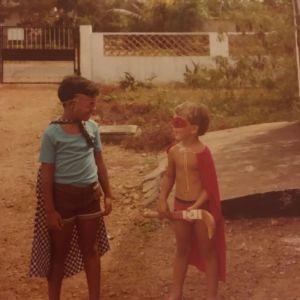 Kaksi poikaa leikkii supersankareita pihalla. Molemmilla pojilla on viitat ja kasvonaamiot. Toinen pojista pitää kädessään maahockey-mailaa. Taustalla näkyvät pihan portti ja aita.