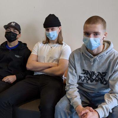 Aleksi Tarkiainen, Janne Käki ja Marius Pellinen istuvat Tikkurilan lukion aulassa.