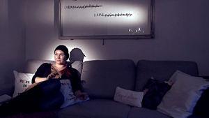 Wilma Dufva istuu sohvalla.