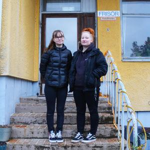 Två unga kvinnor i svarta ytterkläder står på en trappa utanför ett gult hus. På väggen finns en skylt där det står frisör.