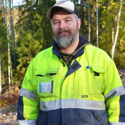 En medelålders man i arbetskläder står i en höstig skog. Han ser in i kameran.