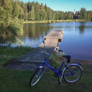Sininen polkupyörä rannalla, taustalla laituri ja vettä
