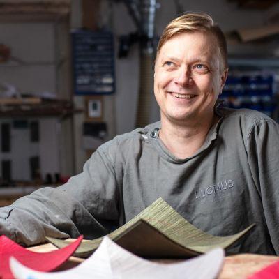 Ville Naumanen istuu puusepänverstaalla, etualalla puuesineitä.