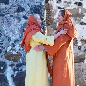 Två kvinnor i långa klänningar och huvuddukar håller om varandra och ser glada ut. Det är två skådespelare som spelar Johanna från Galileen och Maria från Magdalena. Bakom dem synns en stenvägg i solljus.
