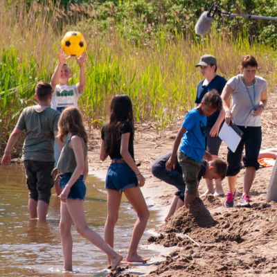 En filminspelning. Barn och personal på en badstrand.