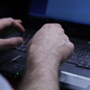 Två händer som skriver på en bärbär dator i halvmörker.