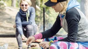 Kristiina Komulainen laittaa ruokaa nuotiopaikalla.
