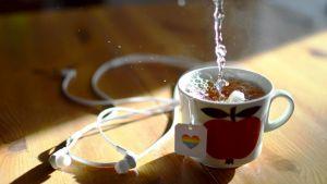 En kaffekopp med ett äpple på. I koppen finns té, på tepåsens logo finns ett hjärta i regnbågsfärger.