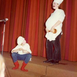 Kaksi lasta istuu rooliasuissan näyttämöllä esiripun edessä. Pojat ovat pukeutuneet kokeiksi.