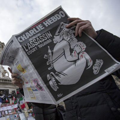 Ranskalaisesen Charlie Hebdo -lehden keskiviikkona ilmeestyneen erikoisnumeron kannessa on esitettynä Jumala, jolla on verta käsissä ja rynnäkkökivääri selässä.