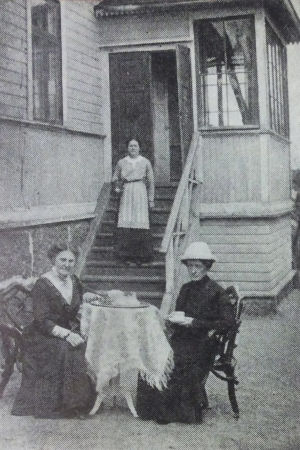 Selma Kajanus ja Lilly Londén kahvittelevat huvilansa edustalla.