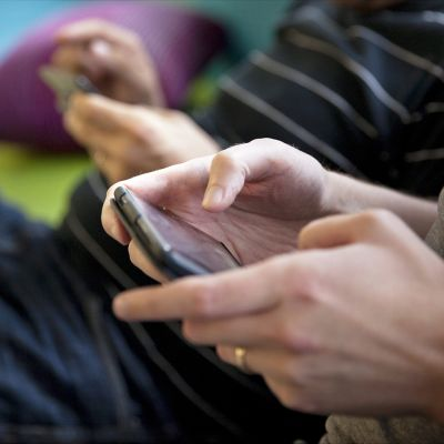 Pariskunta selailee nettiä matkapuhelimilla.