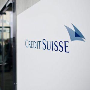 """Skylt där det står """"Credit Suisse"""" i bildens vänstermiljö ser man personer gå in samma byggnad som har skylten."""