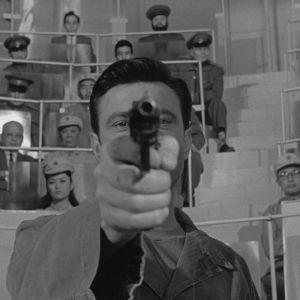 Raymond Shaw (Laurence Harvey) osoittaa pistoolilla suoraan kameraan elokuvassa Mantshurian kandidaatti (1962). Taustalla kiinalaisia ja neuvostoliittolaisia tarkkailijoita