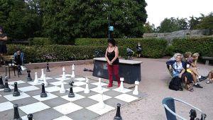 En äldre kvinna spelar schack med stora pjäser i en park.