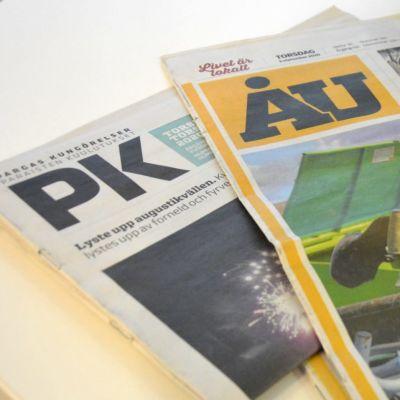 Tidningarna ÅU och Pargas kungörelser på ett bord.