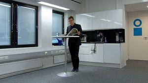 Tommi Vasankari lukee lehteä seisaaltaan työpaikan kahvihuoneessa.