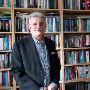 Porträttfoto av Kenneth Gustavsson framför välfylld bokhylla.