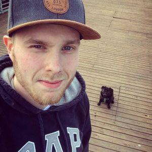 En man i keps står på en terass och tittar in i kameran. I bakgrunden sitter en liten svart hund av rasen mops.