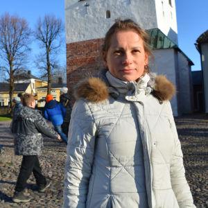 En kvinna i vit jacka står framför klocktornet vid Borgå domkyrka. Bakom henne syns två lekande barn och en kvinna i svart jacka som går förbi.