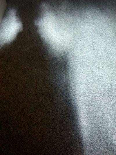 Henkilöstä lankeaa varjo lattialle takana olevan ikkunan valossa.