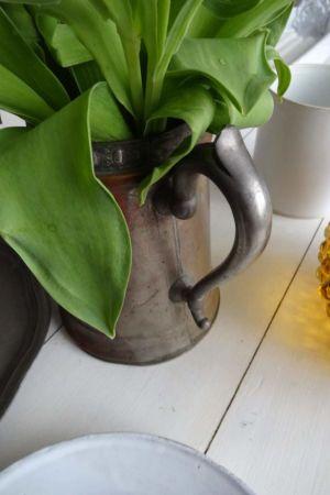 Tulpaner i en gammal kanna av mässing.