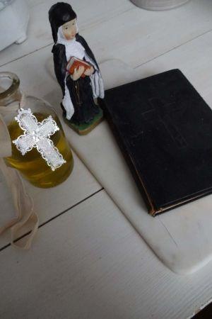 En staty av en nunna brevid en gammal bibel.
