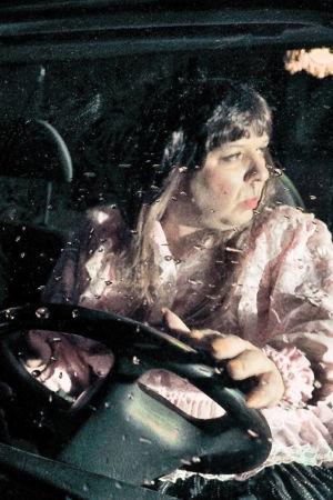 Pariskunta ajaa asuntoautoa sateessa. Kuvassa ohjaamo, jossa istuu mies ja nainen. Kuvassa näyttelijät Angelika Meusel ja Kai Tanner.