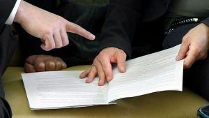 Närbild av dokument på bord och människor omkring.