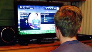 En pojke spelar FIFA 15 på datorn.
