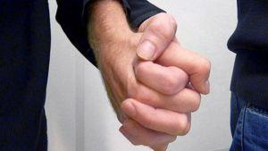 Två män håller varandra i handen.