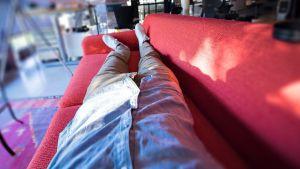 Studerande ligger på soffa