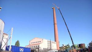 Arbetare i kran nedmonterar sockerfabrikens skorsten i Nådendal.