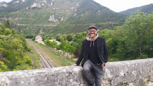Juha Fiilin istuu sillan reunalla kauniissa vihermaisemassa.