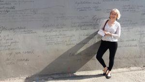 En kvinna vid en stenvägg som täcks av sirliga bokstäver.