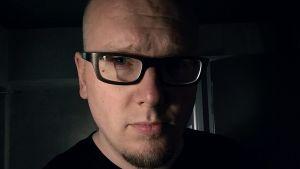 en bild tagen rakt framifrån av matti-pekka ritvolas ansikte. Han bär svart t-skjorta, svartbågade glasögon.