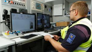 Tulltjänsteman granskar röntgenbilder från lastbilar och containrar.