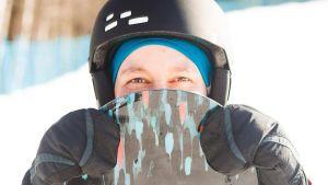 Kvinnas ansikte bakom snowboard