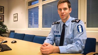 Manlig polis sitter vid ett bord omgärdat av kontorsstolar.