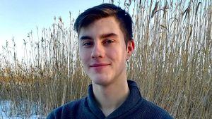 benjamin nedergård i kofta med arrmarna i kors. han står utomhus på vintern med vass i bakgrunden.