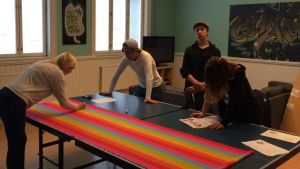 Isabelle Hyytiäinen, Emil Thuesen, Milton Bäcksbacka och Emilie Jäntti jobbar på att göra en regnbågsbanderoll.