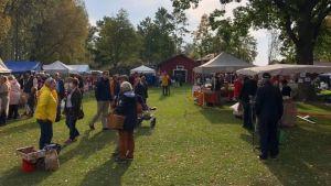 Människor på en marknad på en gräsplan.