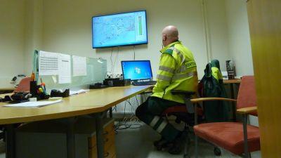 En man i reflexrock sitter på ett kontor framför en stor skärm som visar en karta.